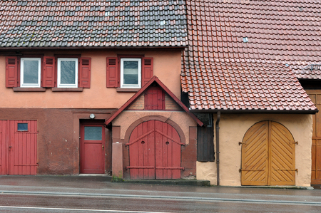 pitched: Facade of an old building with the entrance gate red and orange and a pitched tiled roof. Waiblingen, Baden-Wurttemberg, Germany.