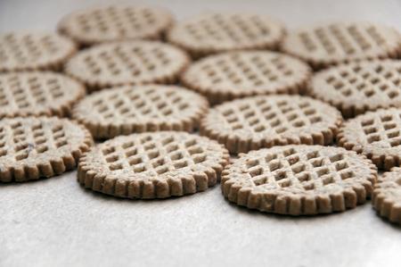 galletas integrales: Fondo del alimento. Un bajo número de galletas de salvado redondas dispuestas en una superficie de cartón en perspectiva. De cerca.