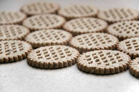 Food background. A lot round bran cookies laid out on a cardboard surface in perspective. Close up.