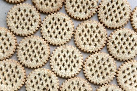galletas integrales: Fondo del alimento. Un bajo número de galletas de salvado redondas dispuestas en una superficie de cartón. Vista superior.