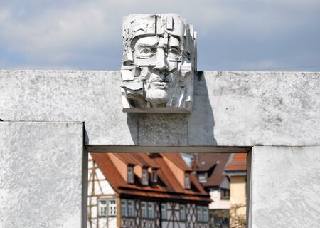 Bietigheim, Germany - April 19, 2016: Modern urban sculpture in Bietigheim, Baden-Wurttemberg. Stylized concrete head of a man close up on a background of the old city.