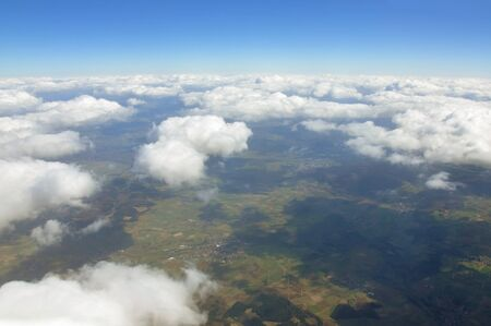 cumulus: Sky scenery. Aerial view over the cumulus clouds and ground on a sunny day. Stock Photo