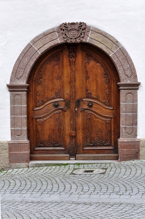 Arched wooden door of an old stone building with decorative carved elements. Waiblingen, Baden-Wurttemberg, Germany. Stock Photo