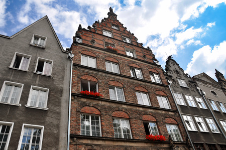 Looking up at the old house with the decor and flowers on the windows against the sky with clouds. Gdansk, Poland. Stock Photo