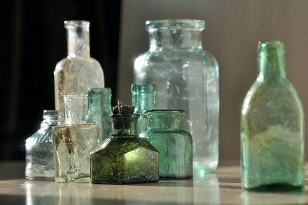 Small different green and white glass vintage bottle closeup.