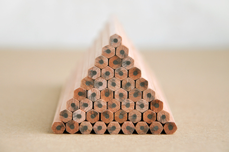 trapeze: Wooden pencils with gray slate stacked in a pyramid shape on a brown surface in perspective.