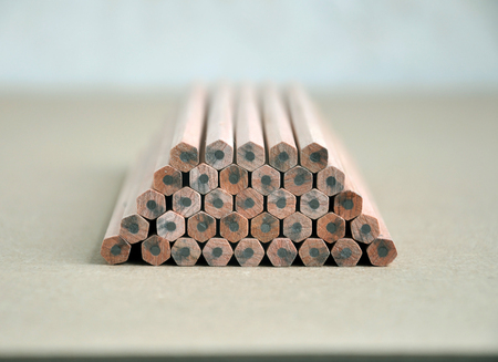 trapeze: Wooden pencils with gray slate lie on each other on brown surface in perspective. Stock Photo