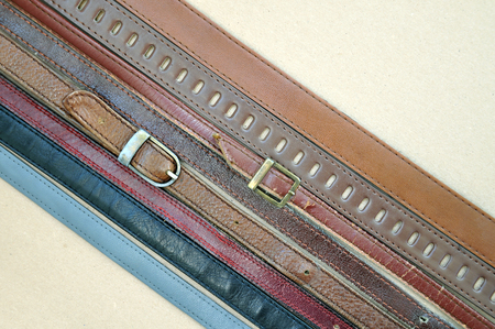 Fashion background. Vintage brown leather belts on a beige cardboard surface located diagonally closeup. Stock Photo