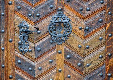 Vintage wooden door texture with round metal elements. Stock Photo