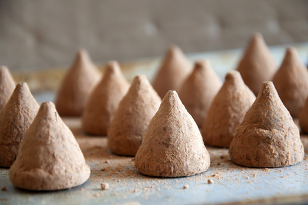 The process of making chocolate truffles. Many candy on a baking sheet dusted with cocoa. Close-up. Stock Photo