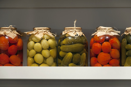 Collection of jars with canned vegetables on white shelf close up. Tomatoes and cucumbers in the winter.