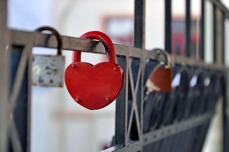 Black metal fence with hanging red closed padlock in the shape of heart close up. Stock Photo