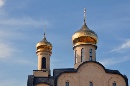 Grodno, Belarus - May 27, 2016: Modern Orthodox Church St. Seraphim of Sarov in the village Obukhovo, Grodno region, Belarus. Front facade with gold domes against the blue sky.