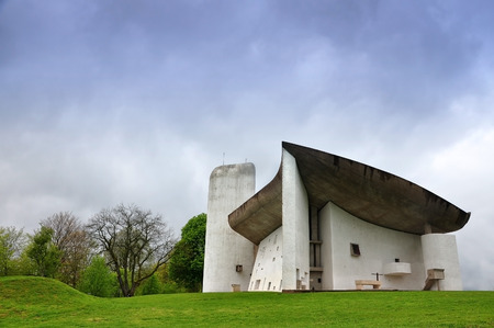RONCHAMP, FRANCE - APRIL 23, 2016: Pilgrimage Church of Notre Dame du Haut in Ronchamp in the Vosges mountains. Facade on the background of mountain scenery. The architect is Le Corbusier. Franche-Comt� �, France.
