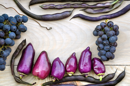 Autumn Food background. Violet bell peppers, purple beans, blue grapes on a light wooden background. The empty space in the center. Stock Photo