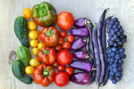 Autumn food background. Beans, grapes, tomatoes, peppers, cucumber on light wooden surface. Top view.