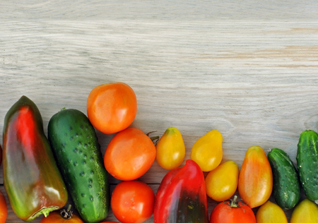 Crop of yellow and red tomatoes, cucumbers, sweet peppers on light wood surface. Top view, place for text.
