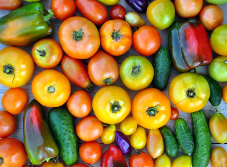 Crop of yellow and red tomatoes, cucumbers, sweet peppers. Food background. Top view.