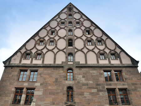 Historic building in Nuremberg, Germany. The front facade of stone blocks with round decorative elements and with a pitched roof. Lookup. Stock Photo