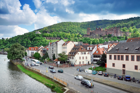 HEIDELBERG, GERMANY - APRIL 20, 2014: Heidelberg Panorama. Waterfront, old buildings, road and castle against the green mountain. Baden-Wurttemberg, Germany in spring.