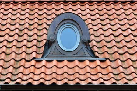 Round decorative dormer windows in the red tiled roof.