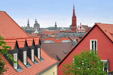 Panorama of Wurzburg with ancient towers of churches. Pitched tiled roof in the foreground. Bavaria, Germany.