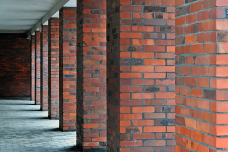 Architectural composition. Many red brick square columns in perspective. Stock Photo