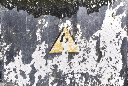 erased: Grunge texture of gray surface with traces of white peeling paint. Erased sign electric shock hazard. Stock Photo