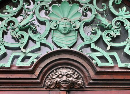 forge: Detail of the entrance to the old building in Prague. Vintage decorations over the door based on curves shapes and stylized faces. Prague, Czech Republic Stock Photo