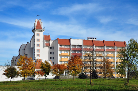 Grodno, Belarus - October 13, 2016: Multistory building of the nursing home with a tower, balconies and red roof in Grodno in the autumn.