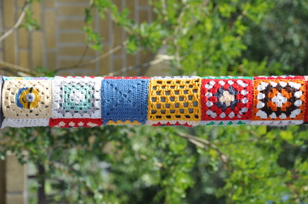 A street pole, tied with colored woolen threads with a pattern. Close up. Selective focus.