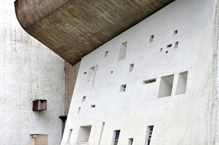 RONCHAMP, FRANCE - APRIL 23, 2016: Pilgrimage Church of Notre Dame du Haut in  Ronchamp.White facade with different windows. The architect is Le Corbusier. Franche-Comte, France.