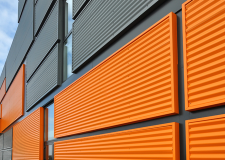Architectural background. Wall of the modern orange and black corrugated metal panels. Фото со стока
