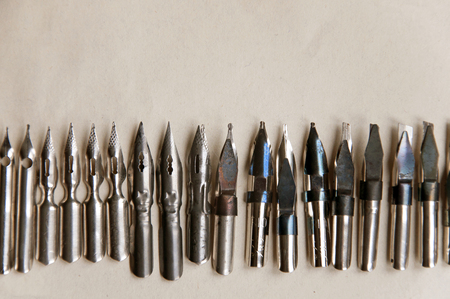 Many metal pens for calligraphy on paper closeup. Top view with empty space.