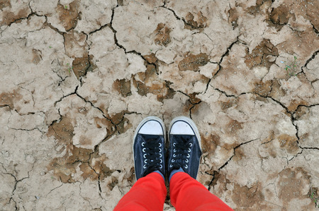 quake: Legs in the red pants and sneakers on sandy ground with cracks. Look down.