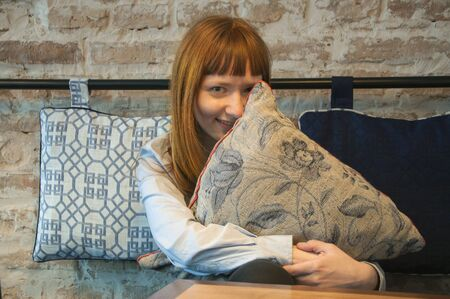 Red-haired smiling and hiding behind a pillow young European girl in a cafe on a brick wall background.