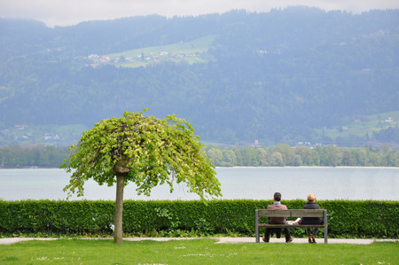 Man and woman sitting on a bench and a tree on a background of Lake Constance and the mountains. Lindau, Germany