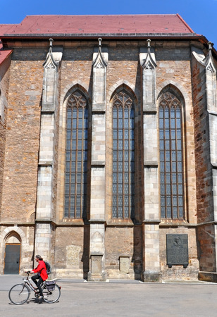 buttresses: Side facade of the old Gothic church with buttresses. Woman on the bicycle in the foreground. Kirchheim Teck, Baden-Wurttemberg, Germany.