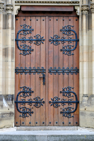 johannes: Entrance to the Gothic Johannes church. Wooden brown doors with metallic floral pattern, Stuttgart, Germany.