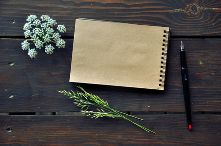 Mock up of craft paper notepad on dark wooden table with forest herbs. Top view.