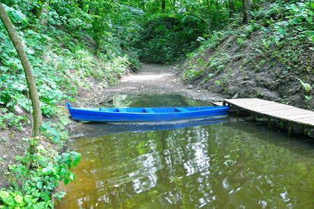 Blue wooden boat on the river bank in bay.