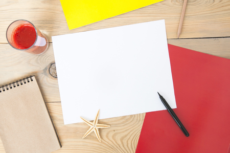 White blank paper sheet on a wooden table with red and yellow paper, strawberry juice and pen. Mock up, top view.