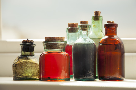 Many antique glass bottles with colored liquids close up. For the pharmacy, oil, cosmetics.