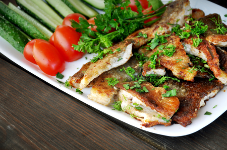 Fried fish with fresh tomatoes, cucumbers and parsley on a white dish. Close up. Lizenzfreie Bilder