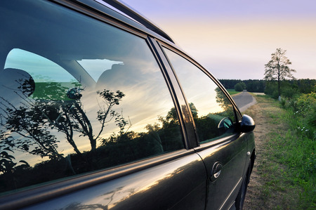 road shoulder: A glass of standing car reflecting the countryside landscape during the sunset in summer. Stock Photo