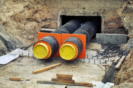 The process of laying of engineering heating systems. Two black plastic pipes with yellow bases in sandy trench going underground.