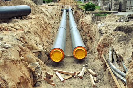 The process of laying of engineering heating systems. Two black plastic pipes with yellow bases in sandy trench in perspective. Reklamní fotografie - 81561479
