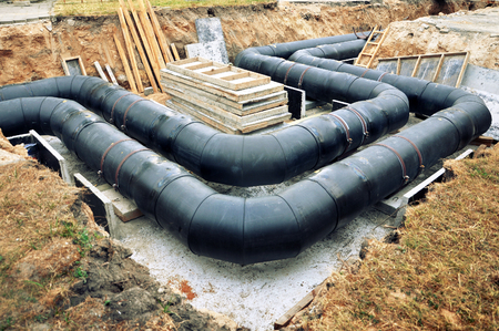 The process of laying of engineering heating systems. Two turning black plastic pipes in sandy trench. Reklamní fotografie - 81508617