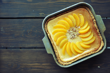 Homemade cheesecake with peaches in metal form for baking on a brown wooden background. Top view.