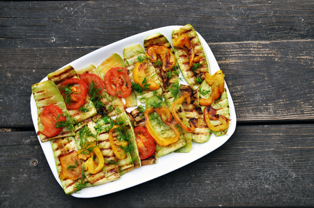 White rectangular dish with grilled zucchini and tomatoes on a rustic wooden brown surface.